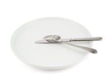 Επιτραπέζιο μαχαίρι, δίκρανο και κεραμικό πιάτο που απομονώνονται Στοκ Φωτογραφία