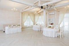 Επιτραπέζιο ντεκόρ με τα άσπρα λουλούδια και τα κεριά για μια δεξίωση γάμου στοκ εικόνες