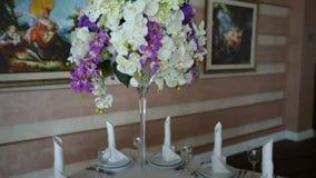 Επιτραπέζιο σκεύος και ντεκόρ των ανθοδεσμών των λουλουδιών για τη δεξίωση γάμου απόθεμα βίντεο