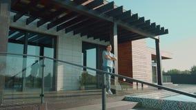 Επιτυχές άτομο που μένει στο πεζούλι Πλούσιος άνθρωπος που στέκεται στο μέρος διαμερισμάτων πολυτέλειας απόθεμα βίντεο