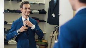Επιτυχές άτομο που φορά ένα σακάκι στη μπουτίκ φιλμ μικρού μήκους