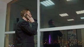 Επιτυχές επιχειρησιακό άτομο που καλεί στο κινητό τηλέφωνο στο υπόβαθρο παραθύρων βραδιού απόθεμα βίντεο