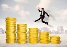 Επιτυχές επιχειρησιακό άτομο που πηδά επάνω στα χρυσά χρήματα νομισμάτων Στοκ Εικόνες