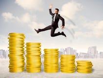 Επιτυχές επιχειρησιακό άτομο που πηδά επάνω στα χρυσά χρήματα νομισμάτων Στοκ Φωτογραφία