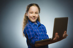 Επιτυχές ευτυχές κορίτσι που χρησιμοποιεί απομονωμένο το lap-top γκρίζο υπόβαθρο Στοκ Φωτογραφίες