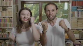 Επιτυχές ευτυχές χιλιετές ζεύγος που γιορτάζει το επίτευγμα ενθαρρυντικό και που χορεύει - απόθεμα βίντεο