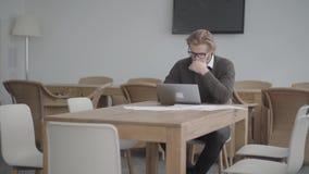 Επιτυχές ξανθό στοχαστικό άτομο πορτρέτου στα γυαλιά που κάθεται στον πίνακα σε ένα ελαφρύ άνετο γραφείο μπροστά από φιλμ μικρού μήκους