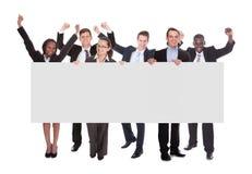 Επιτυχές businesspeople που κρατά τον κενό πίνακα διαφημίσεων Στοκ Εικόνες