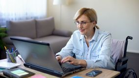 Επιτυχής ανώτερη γυναίκα στην αναπηρική καρέκλα που λειτουργεί στο lap-top, που κουβεντιάζει με τον πελάτη απόθεμα βίντεο