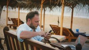 Επιτυχής αρσενικός ανεξάρτητος τουρίστας εργαζομένων που χρησιμοποιεί τις αγορές app smartphone καθμένος καρέκλα παραλιών θερινού απόθεμα βίντεο