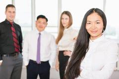 Επιτυχής ασιατική επιχειρησιακή γυναίκα με την επιχειρησιακή ομάδα Στοκ Εικόνα