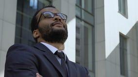 Επιτυχής αφροαμερικανός επιχειρηματίας που στέκεται κοντά στο κτίριο γραφείων, κινηματογράφηση σε πρώτο πλάνο φιλμ μικρού μήκους