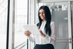 Επιτυχής βέβαια επιχειρησιακή γυναίκα που εργάζεται με την ταμπλέτα σε μια ρύθμιση γραφείων στοκ φωτογραφίες