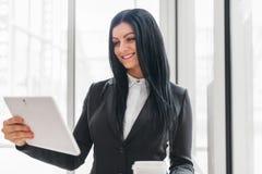 Επιτυχής βέβαια επιχειρησιακή γυναίκα που εργάζεται με την ταμπλέτα σε μια ρύθμιση γραφείων στοκ φωτογραφία με δικαίωμα ελεύθερης χρήσης