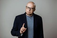 Επιτυχής βέβαιος επιχειρηματίας στα γυαλιά που μιλά πέρα από το μπεζ υπόβαθρο στοκ εικόνα με δικαίωμα ελεύθερης χρήσης