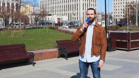 Επιτυχής δημοσιογράφος ειδήσεων με τη διαθέσιμη ομιλία μικροφώνων ζωντανή στην οδό απόθεμα βίντεο