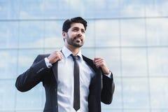 Επιτυχής επιχειρηματίας ή εργαζόμενος που στέκεται στο κοστούμι και που ισιώνει το σακάκι Στοκ Φωτογραφίες