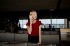 επιτυχής επιχειρηματίας γυναικών που καλεί με το τηλέφωνο κυττάρων στεμένος στο σύγχρονο εσωτερικό εστιατορίων Στοκ Εικόνα