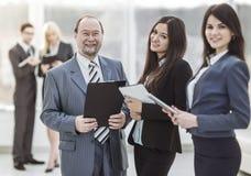 Επιτυχής επιχειρηματίας και δύο βοηθοί του με τα έγγραφα σχετικά με το υπόβαθρο του σύγχρονου γραφείου στοκ εικόνα με δικαίωμα ελεύθερης χρήσης