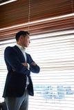 Επιτυχής επιχειρηματίας με τα διασχισμένα όπλα που σκέφτεται για κάτι στεμένος κοντά στο παράθυρο με τους ενετικούς τυφλούς στοκ φωτογραφία
