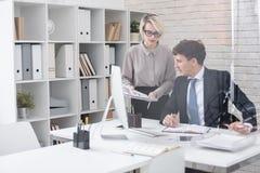 Επιτυχής επιχειρηματίας με το γραμματέα στην αρχή στοκ εικόνες