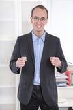 Επιτυχής επιχειρηματίας με το κοστούμι και τις κλειστές πυγμές που χαμογελά μακριά Στοκ Φωτογραφία