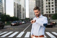 Επιτυχής επιχειρηματίας που ελέγχει το χρόνο στο ρολόι υπαίθριο Στοκ Εικόνες