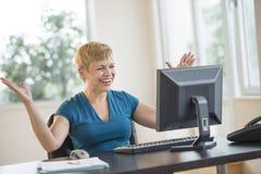 Επιτυχής επιχειρηματίας που εξετάζει τον υπολογιστή Στοκ Φωτογραφίες