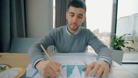Επιτυχής επιχειρηματίας που εργάζεται με το σχέδιο καινοτομίας, που κάθεται στον πίνακα στον καφέ απόθεμα βίντεο