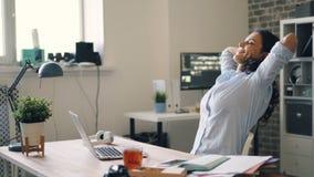 Επιτυχής επιχειρηματίας που εργάζεται με το lap-top που χαλαρώνει έπειτα το αίσθημα χαμόγελου ευτυχής φιλμ μικρού μήκους
