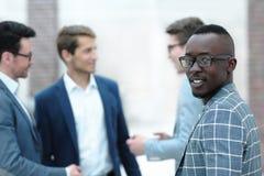 Επιτυχής επιχειρηματίας που στέκεται σε ένα σύγχρονο γραφείο στοκ εικόνες