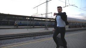 Επιτυχής επιχειρηματίας που τρέχει μέσω του σιδηροδρομικού σταθμού και που εξετάζει το ρολόι Ο νεαρός άνδρας είναι πρώην για το τ απόθεμα βίντεο