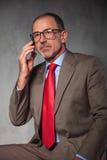 Επιτυχής επιχειρηματίας που φορά τα γυαλιά που καλούν με το smartpho του Στοκ Εικόνα
