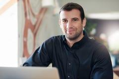 Επιτυχής επιχειρηματίας που χαμογελά και που χρησιμοποιεί ένα lap-top σε ένα γραφείο Στοκ Φωτογραφία