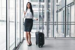 Επιτυχής επιχειρησιακή γυναίκα με τον καφέ και βαλίτσα σε μια ρύθμιση γραφείων στοκ φωτογραφία