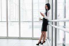 Επιτυχής επιχειρησιακή γυναίκα με τον καφέ και smartphone σε μια ρύθμιση γραφείων στοκ εικόνα με δικαίωμα ελεύθερης χρήσης