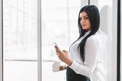 Επιτυχής επιχειρησιακή γυναίκα με τον καφέ και smartphone σε μια ρύθμιση γραφείων στοκ εικόνες