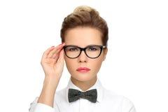 Επιτυχής επιχειρησιακή γυναίκα που φορά τα γυαλιά, ένα άσπρο πουκάμισο με έναν δεσμό τόξων Στοκ Εικόνα