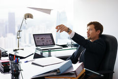 Επιτυχής εργαζόμενος γραφείων ατόμων αφηρημάδας που ρίχνει το αεροπλάνο εγγράφου Στοκ φωτογραφία με δικαίωμα ελεύθερης χρήσης