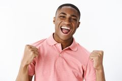 Επιτυχής ευτυχής και ευτυχής όμορφος νέος τύπος αφροαμερικάνων στο ρόδινο πουκάμισο που σφίγγει τις πυγμές στη νίκη και την ευθυμ στοκ εικόνα