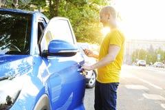 Επιτυχής ευτυχής νεαρός άνδρας και το αυτοκίνητό του στο μαλακό φως ηλιοβασιλέματος στο αστικό υπόβαθρο Επιχειρησιακό άτομο με το στοκ εικόνες με δικαίωμα ελεύθερης χρήσης