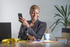 Επιτυχής μαύρη αμερικανική επιχειρησιακή γυναίκα afro που εργάζεται στο σύγχρονο γραφείο με τις κινητές σημειώσεις τηλεφωνικού γρ Στοκ Εικόνες