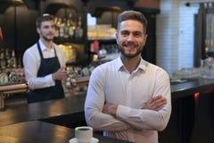 Επιτυχής μικρός ιδιοκτήτης επιχείρησης που στέκεται με τα διασχισμένα όπλα με τον υπάλληλο στο υπόβαθρο που προετοιμάζει τον καφέ στοκ εικόνες