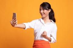Επιτυχής νέα ασιατική γυναίκα με το κινητό τηλέφωνο στοκ φωτογραφίες