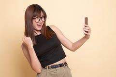 Επιτυχής νέα ασιατική γυναίκα με το κινητό τηλέφωνο στοκ εικόνες