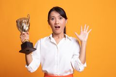 Επιτυχής νέα ασιατική γυναίκα που κρατά ένα τρόπαιο στοκ φωτογραφία