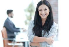 Επιτυχής νέα επιχειρησιακή γυναίκα στο υπόβαθρο γραφείων στοκ φωτογραφία