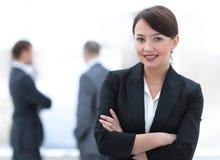 Επιτυχής νέα επιχειρησιακή γυναίκα στο υπόβαθρο του γραφείου Στοκ Εικόνες