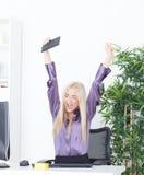 Επιτυχής νέα ξανθή επιχειρηματίας, χειρονομία νίκης, χέρια επάνω, που χαμογελά στο γραφείο Στοκ φωτογραφία με δικαίωμα ελεύθερης χρήσης