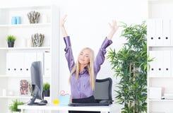 Επιτυχής νέα ξανθή επιχειρηματίας, χειρονομία νίκης, χέρια επάνω, που χαμογελά στο γραφείο Στοκ εικόνα με δικαίωμα ελεύθερης χρήσης
